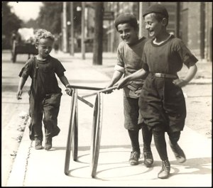 Boys in knickerbockers rolling hoops